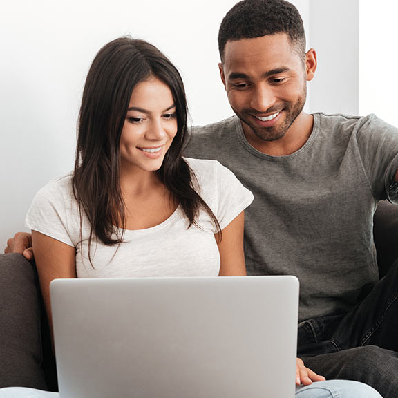 Happy couple on the couch using laptop